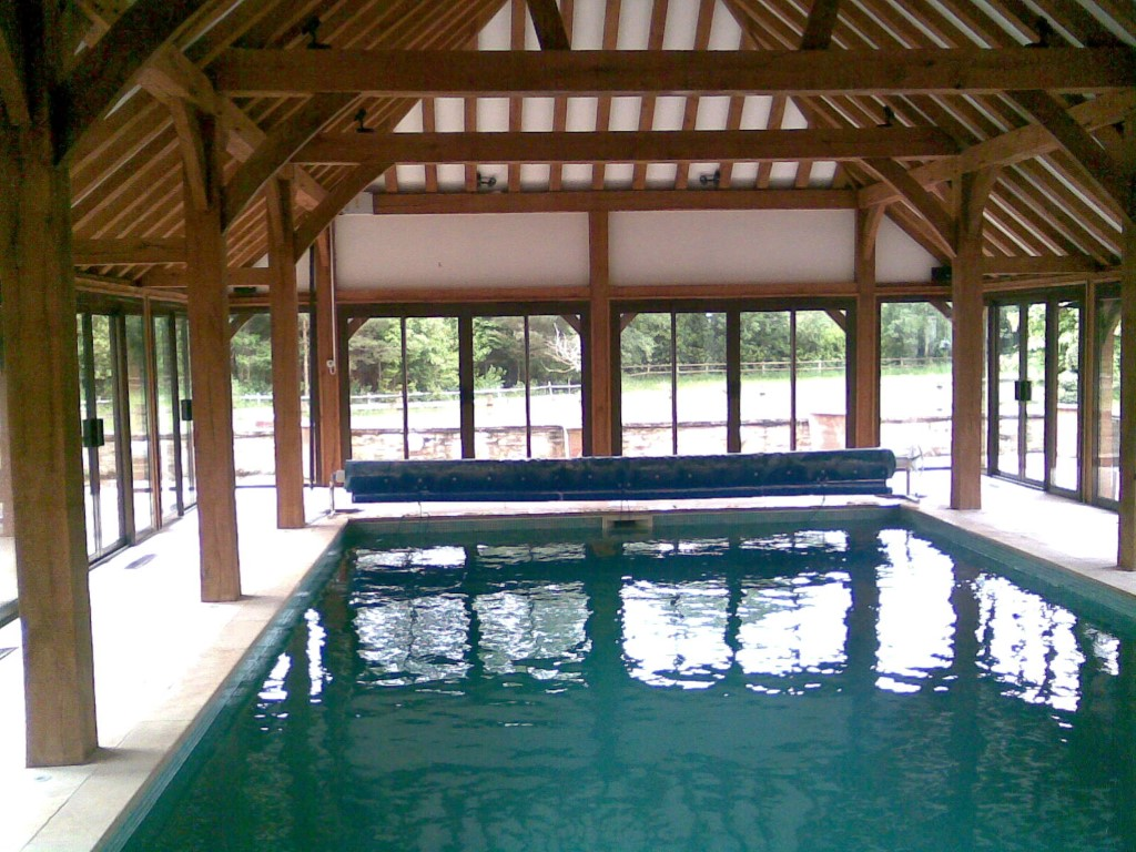 pool inside wooden cover building with cover and reel system