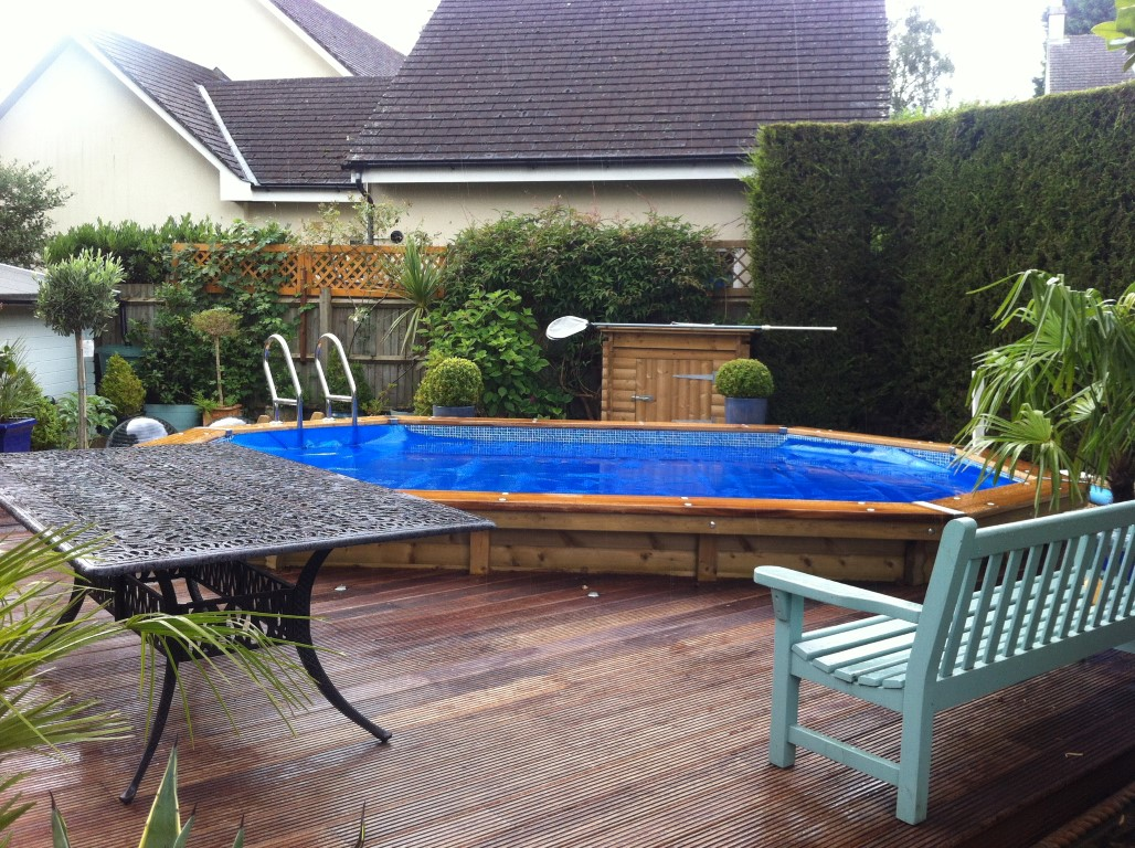 octagonal pool on decking by bench and table