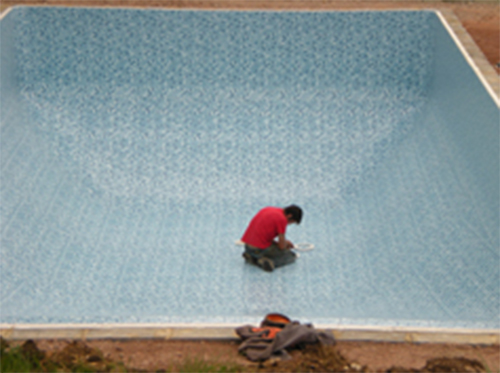 Empty outdoor pool with maintenance man in
