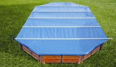 Blue pool cover over wooden pool