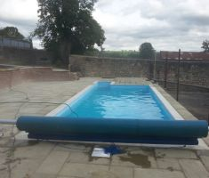 Small outdoor pool construction with cover and reel system