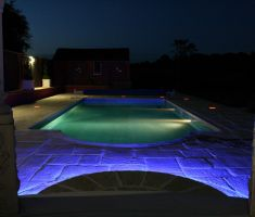 Outdoor pool lit up at night with LED lights