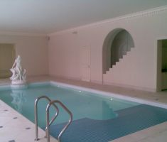 Indoor swimming pool with specialised cover covering half of the pool 2