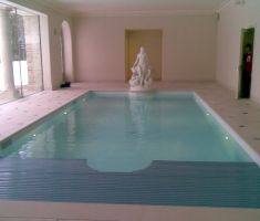 Indoor swimming pool with specialised cover covering half of the pool