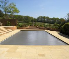 Outdoor pool with grey cover on a sunny day